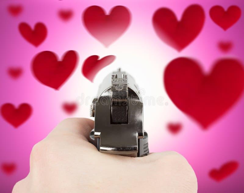 Hand som rymmer en handeldvapen på hjärtabakgrund arkivbilder