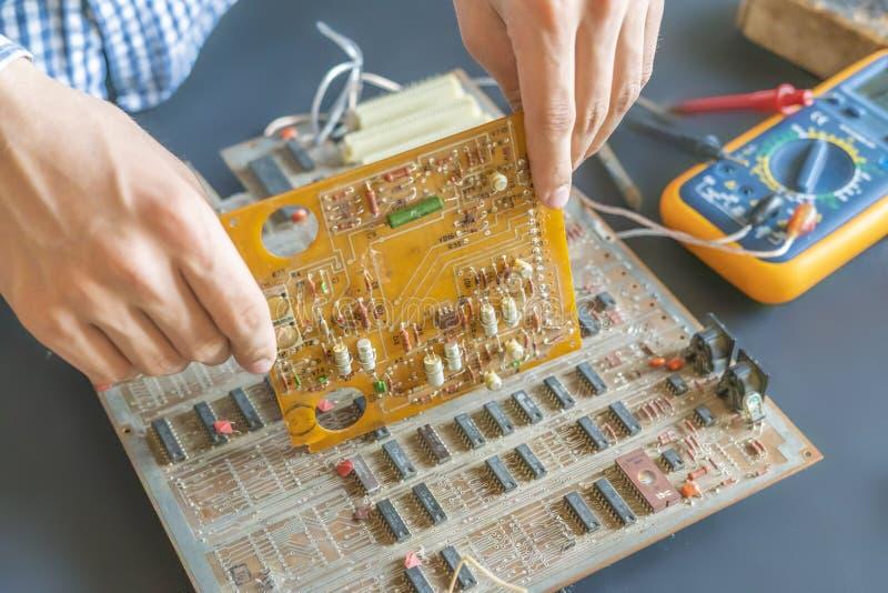Hand som rymmer en knipa för reparation för bräde för elektrisk strömkrets och att montera elektronikbegrepp f royaltyfria bilder