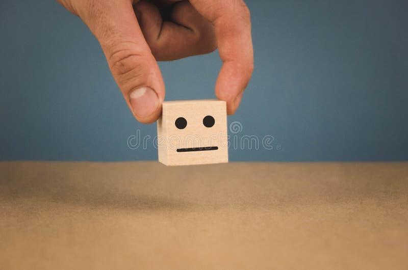 Hand som rymmer en kub med en neutral smiley p? en bl? bakgrund royaltyfri foto