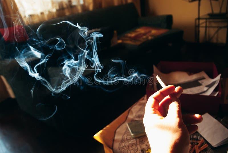 Hand som rymmer en mörk bakgrund för cigarett royaltyfri foto
