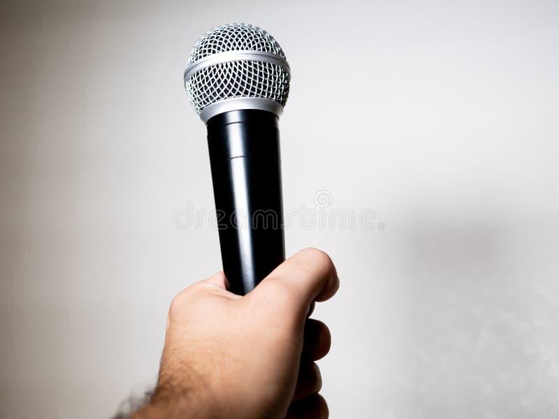 hand som rymmer en mikrofon i vit bakgrund arkivfoton