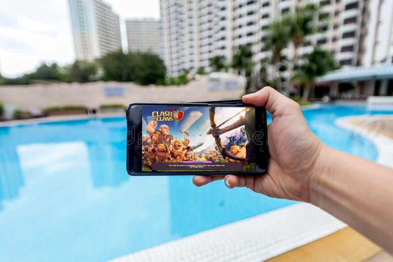 Hand som rymmer en mobiltelefon som spelar sammandrabbning för Supercell` s av klan arkivbilder