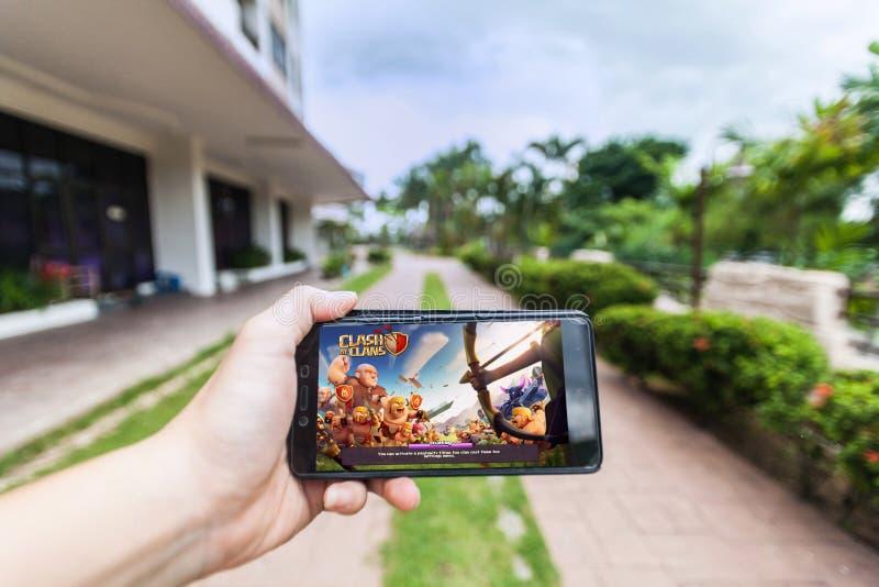 Hand som rymmer en mobiltelefon som spelar sammandrabbning för Supercell` s av klan arkivfoto