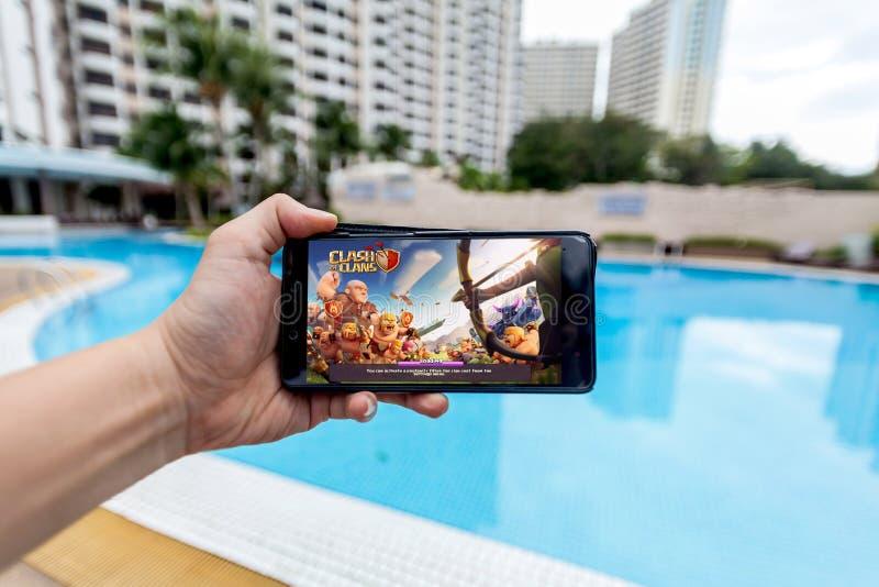 Hand som rymmer en mobiltelefon som spelar sammandrabbning för Supercell` s av klan arkivbild