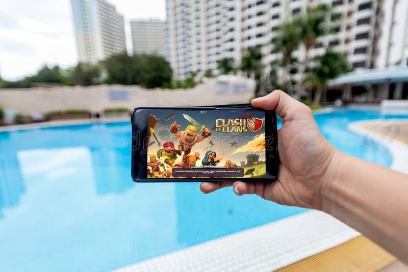 Hand som rymmer en mobiltelefon som spelar sammandrabbning för Supercell` s av klan arkivfoton