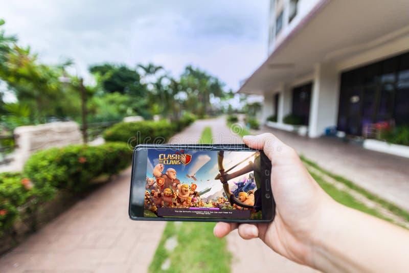 Hand som rymmer en mobiltelefon som spelar sammandrabbning för Supercell` s av klan royaltyfri bild
