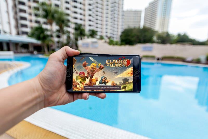 Hand som rymmer en mobiltelefon som spelar sammandrabbning för Supercell` s av klan royaltyfri foto