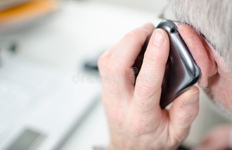 Hand som rymmer en mobiltelefon till hans öra fotografering för bildbyråer