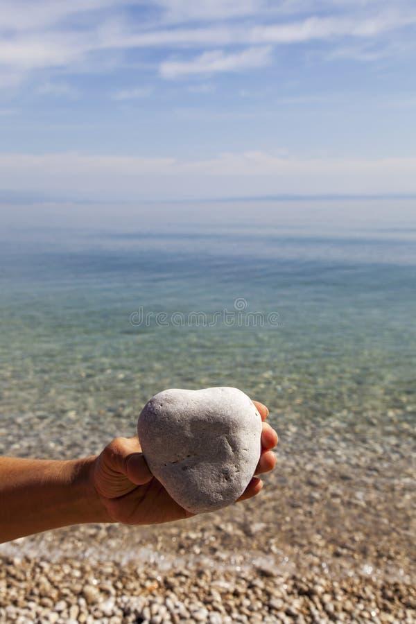 Hand som rymmer en naturlig hjärta-formad sten arkivbild
