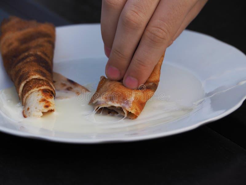 Hand som rymmer en pannkaka med kräm- närbild royaltyfria bilder