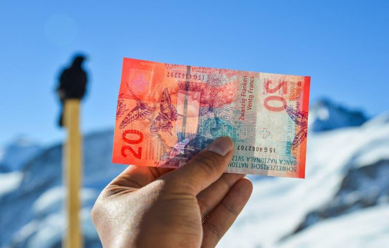 Hand som rymmer en 20 schweizisk franc sedel royaltyfri foto