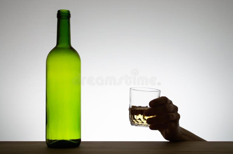 Hand som rymmer ett exponeringsglas av vin arkivbild