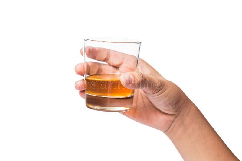 Hand som rymmer ett exponeringsglas av whisky royaltyfri bild
