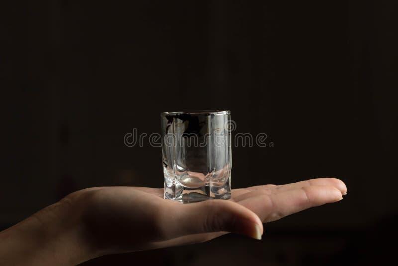 Hand som rymmer ett exponeringsglas på blackbackground arkivbilder