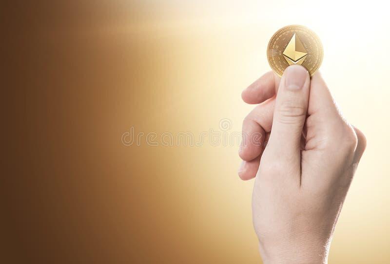 Hand som rymmer ett guld- Ethereum mynt på en försiktigt tänd bakgrund med kopieringsutrymme arkivbild
