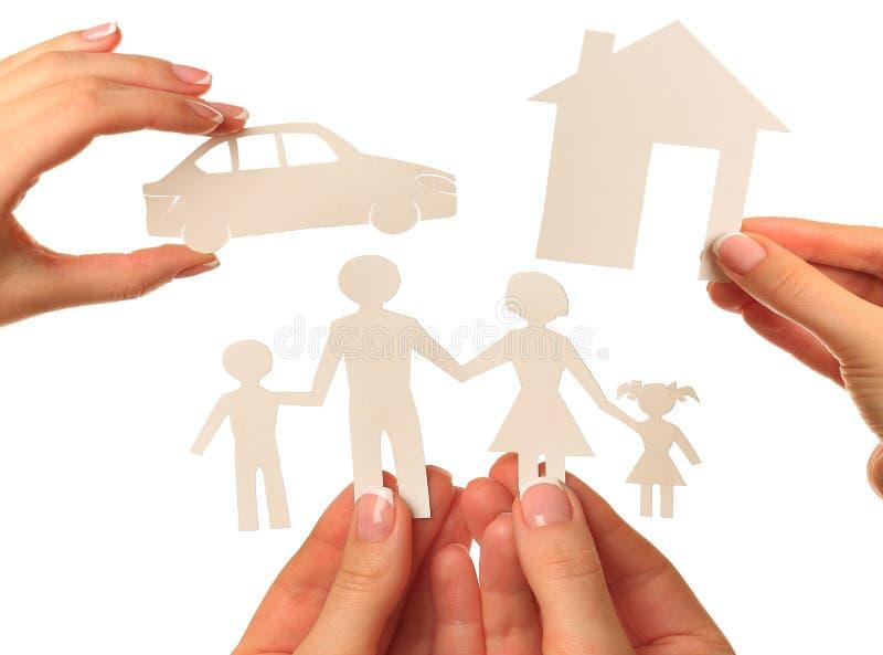 Hand som rymmer ett pappers- hem, bil, familj på vit bakgrund royaltyfria foton