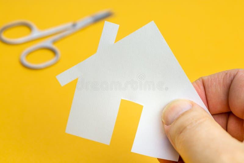 Hand som rymmer ett pappers- hus med ett par av sax i bakgrunden royaltyfria bilder