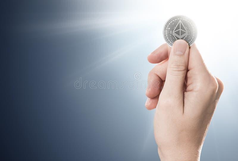 Hand som rymmer ett silverEthereum mynt på en försiktigt tänd bakgrund med kopieringsutrymme arkivbilder