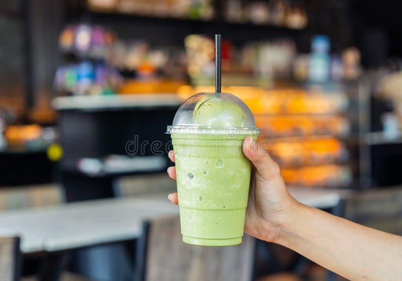 Hand som rymmer exponeringsglas av frappe för grönt te med glass royaltyfria foton