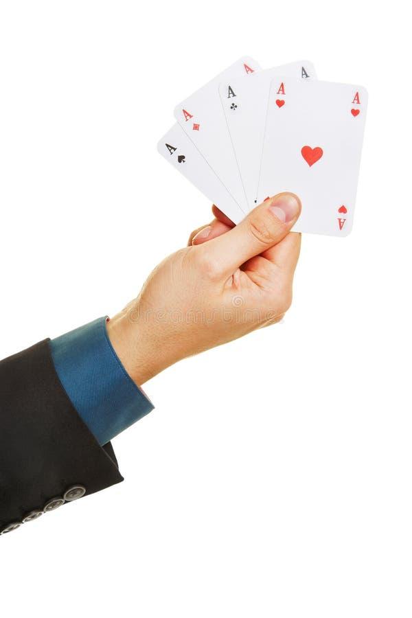 Hand som rymmer fyra överdängare, medan spela poker arkivfoto