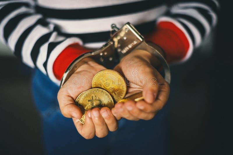 Hand som rymmer guld- Bitcoin Brottslig man med handbojor efter hängivet ett brott arkivbild