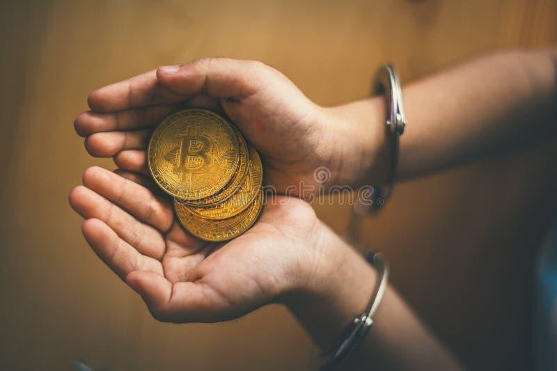 Hand som rymmer guld- Bitcoin Brottslig man med handbojor efter hängivet ett brott fotografering för bildbyråer