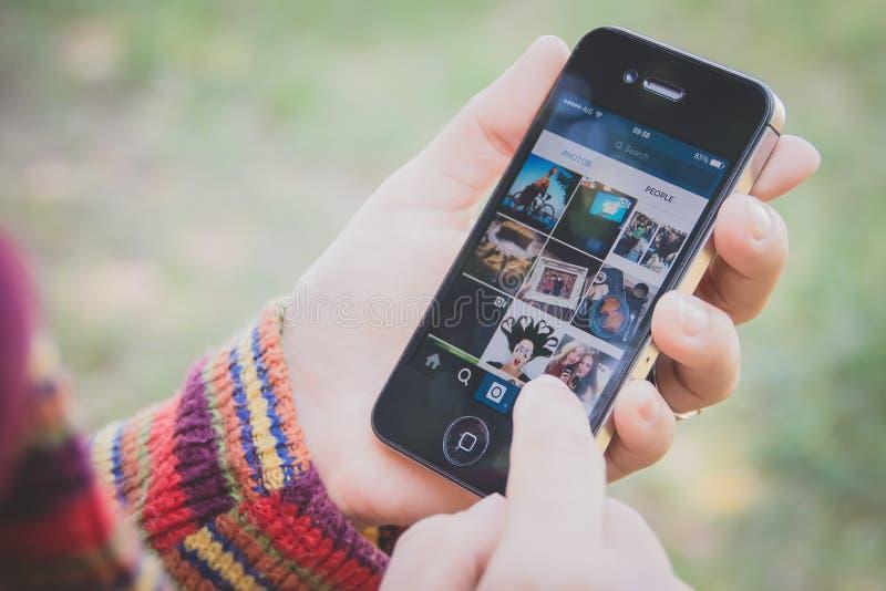 Hand som rymmer Iphone och använder den Instagram applikationen fotografering för bildbyråer