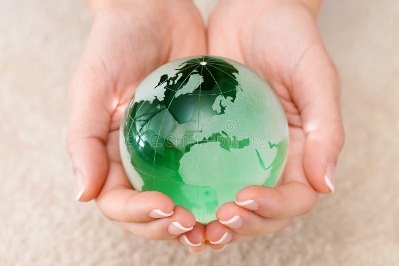 Hand som rymmer jordklotet för grönt exponeringsglas arkivbild