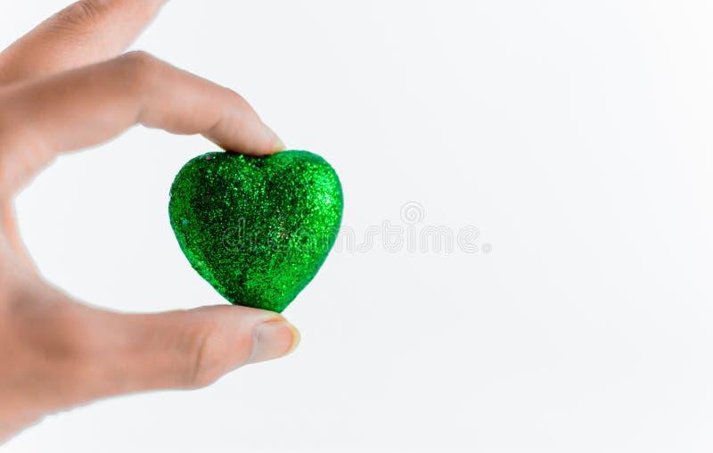Hand som rymmer mini- hjärtor på vit bakgrund arkivbild