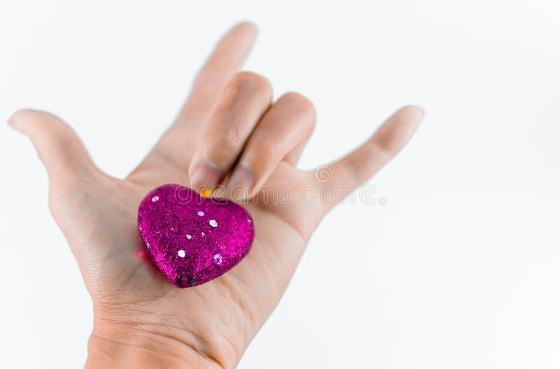 Hand som rymmer mini- hjärtor på vit bakgrund royaltyfri fotografi