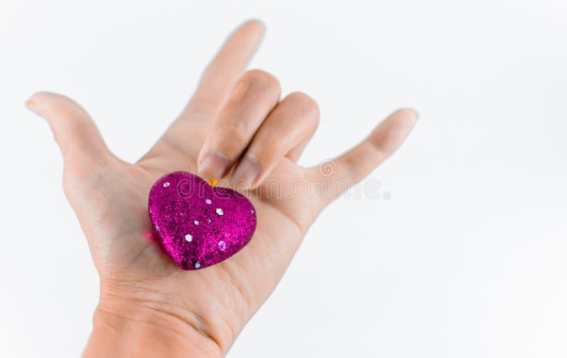 Hand som rymmer mini- hjärtor på vit bakgrund royaltyfria foton