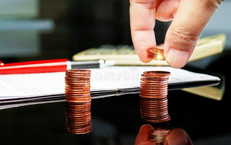 Hand som rymmer mynt över rad av myntet royaltyfri fotografi