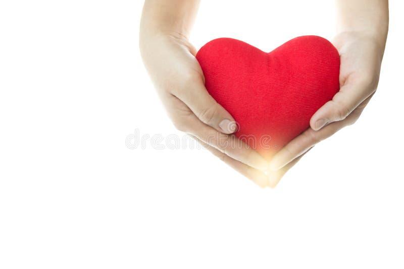 Hand som rymmer röd hjärtaform isolerad arkivfoto