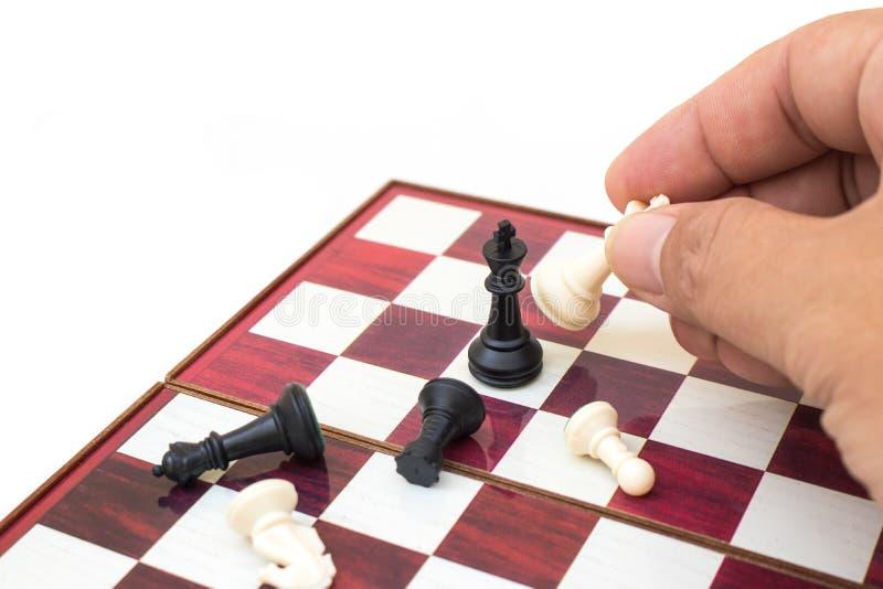 Hand som rymmer schackstycket och spelar schackleken arkivbild