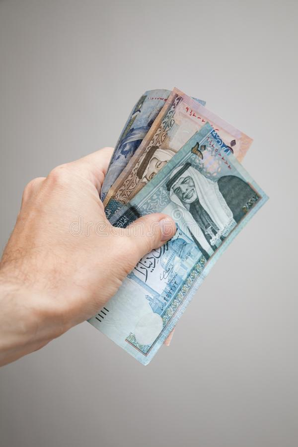 Hand som rymmer sedlar för jordanska dinar fotografering för bildbyråer