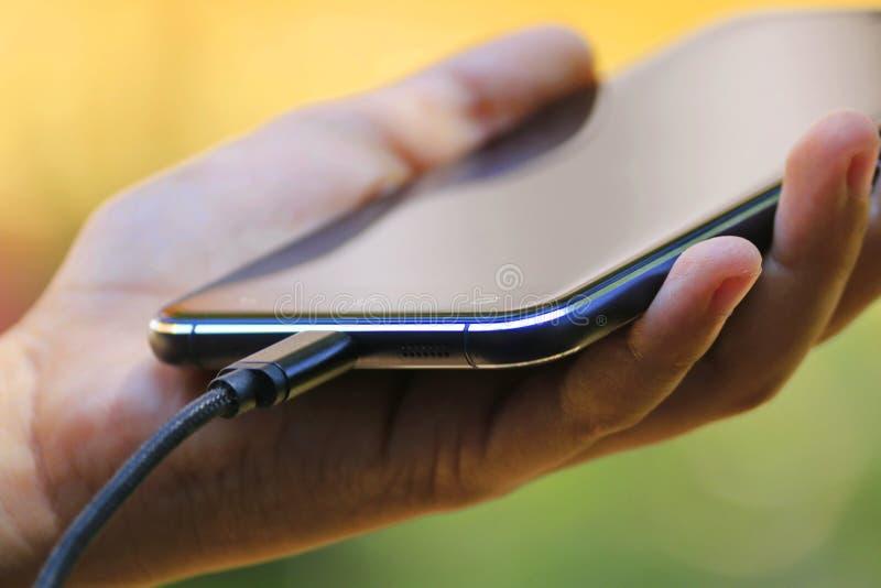 Hand som rymmer telefonen med den laddande kabeln royaltyfri foto