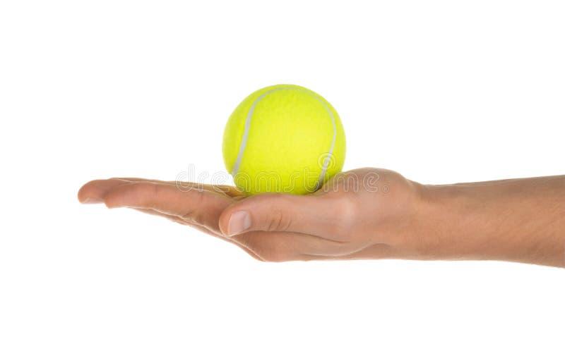 Hand som rymmer tennisbollen isolerad på den vita snabba banan arkivfoto