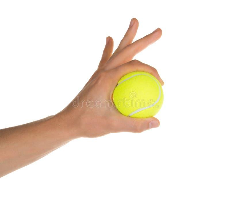 Hand som rymmer tennisbollen isolerad på den vita snabba banan arkivbild