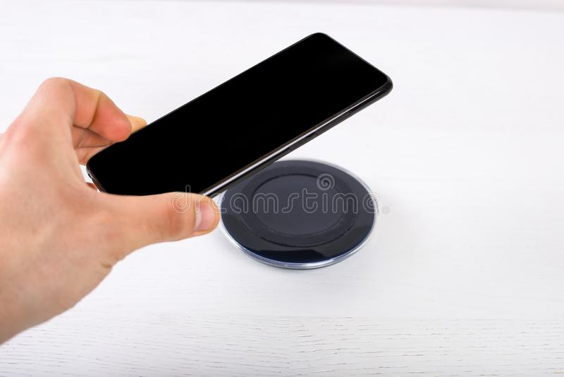 Hand som sätter mobiltelefonen på den trådlösa uppladdaren, modern utrustning på vit bakgrund royaltyfri bild