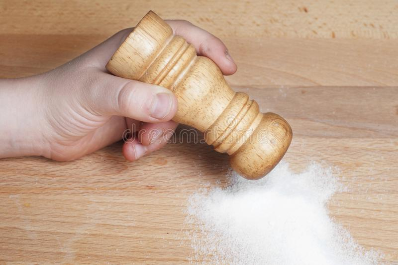 Hand som sätter någon salt shaker arkivbilder