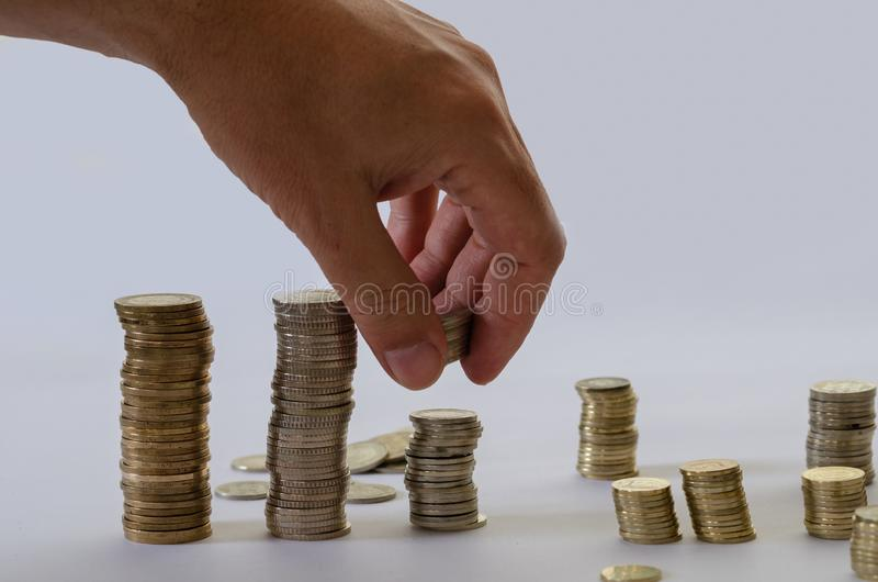 Hand som sätter pengarmyntbunten som växer, sparande pengar för avsikt fotografering för bildbyråer