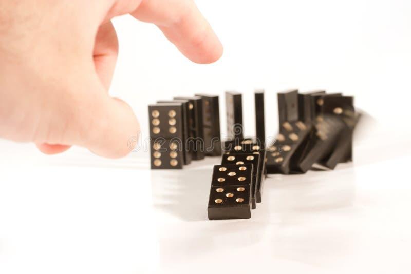 Hand som skjuter en rad av domino royaltyfria foton