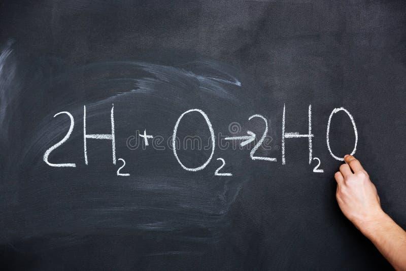 Hand som skriver kemisk formel på svart tavla arkivfoto