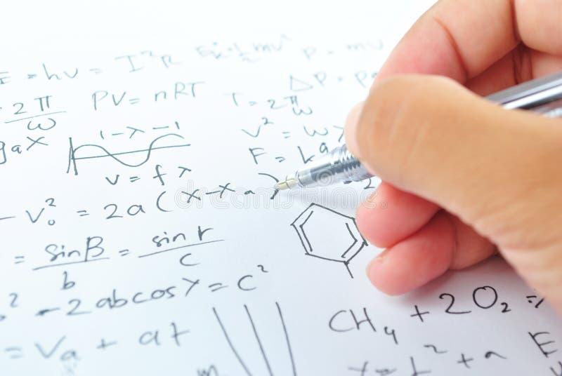 Hand som skriver olik högstadiummatematik och vetenskap royaltyfria foton
