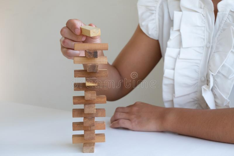 Hand som spelar kvarterträleken som spelar förlägga träkvarteret Begreppsrisk av ledning- och strategiplanet arkivfoto