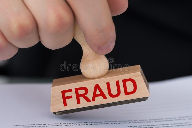 Hand som stämplar dokumentet med den Rubber stämpeln för bedrägeri royaltyfri fotografi