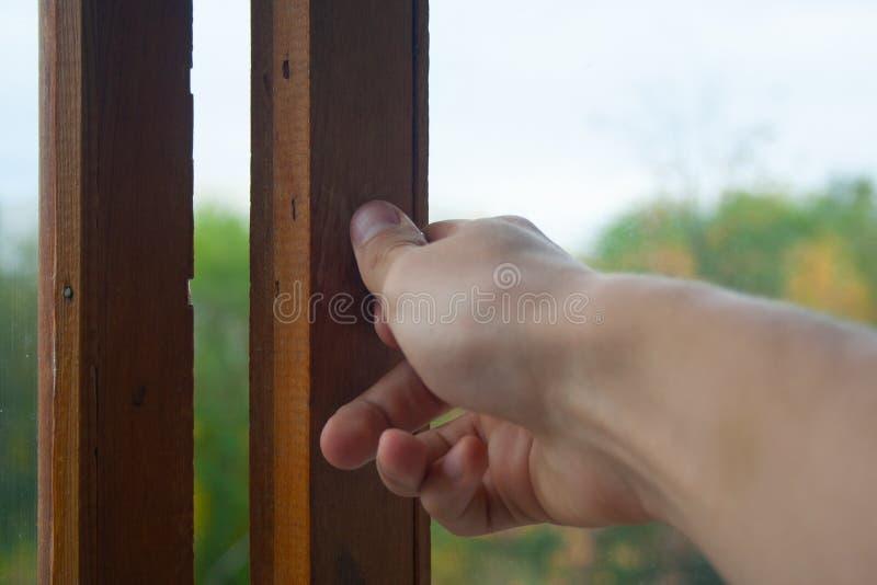 Hand som stänger fönstret royaltyfria bilder