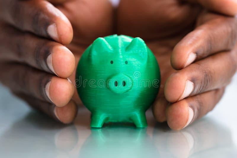 Hand som täcker den gröna Piggybanken royaltyfri fotografi