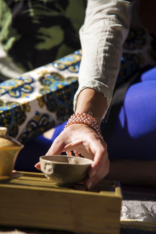 Hand som tar en kopp med ett te royaltyfri fotografi