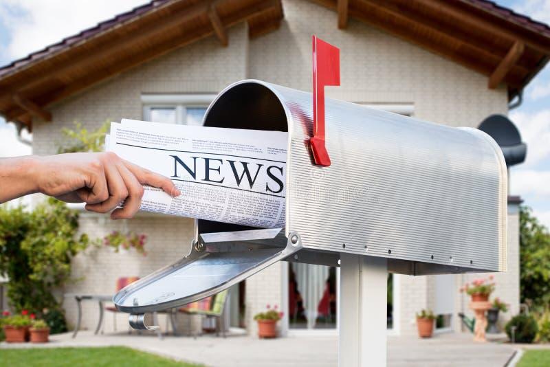 Hand som tar tidningen från brevlåda royaltyfri bild